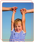 Photo of young boy against blue sky, being lifted in the air by two hands