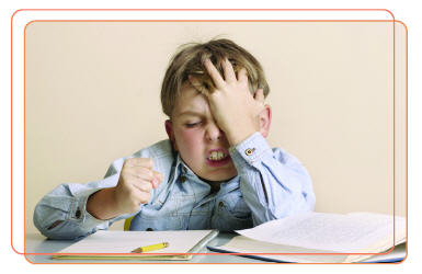 Photo of young boy getting frustrated while doing homework