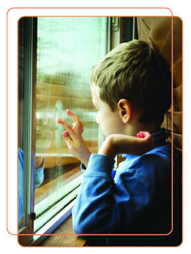 Photo of boy standing at window looking at the rain outside