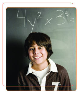 Photo of boy standing in front of blackboard smiling. A maths equation is written on the blackboard in chalk.